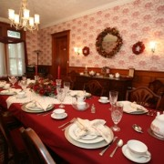 The dining room at Barristers B&B is set with a bright red table cloth, white plates and white napkins