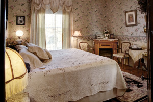 Grandmother's Room at Barristers. Shows the queen bed with a white quilt and the sitting chairs with a small table