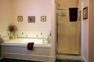 A photo of the bathtub with flowers on the side and the shower.