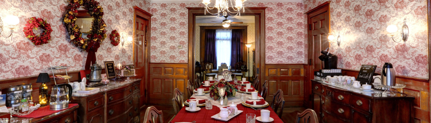 A view of the dining room looking length wise. Red table cloth and matching napkims with white plates