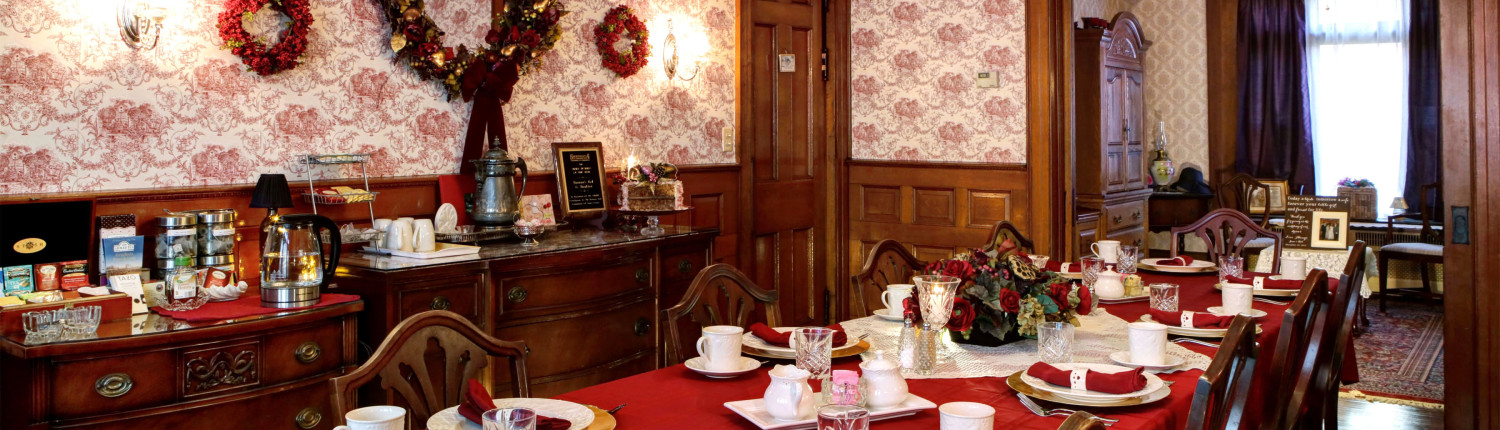 The dining room at Barristers B&B is set with a bright red table cloth, white plates and red napkins