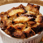 baked french toast in a white cup with baked pineapple on the side.