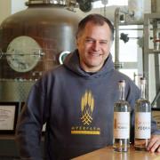 Joe Myer standing with 2 bottles of vodka.