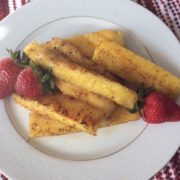 Fried pinapple slices on a plate with strawberries.