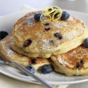 Ricotta Pancakes with blueberries on a white plate.