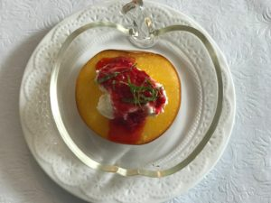 Baked Peach in a glass apple bowl with sauce on top.